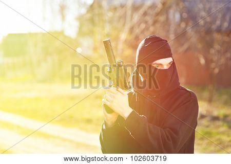 Gunman in black mask holding gun with silencer