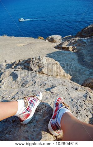 Overhead photo of feet on a background of seaview. Women feets view from above. Exploring, travellin