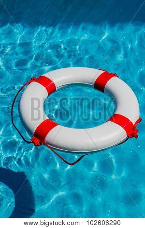 an emergency tire floating in a pool. symbolic photo for rescue and crisis management in the financial crisis and banking crisis.