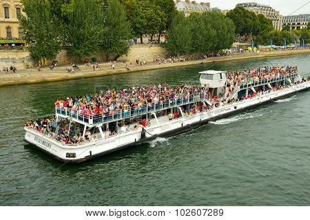 PARIS, FRANCE - AUGUST 09, 2015: tourists sail in the ship. Paris, aka City of Love, is a popular travel destination and a major city in Europe
