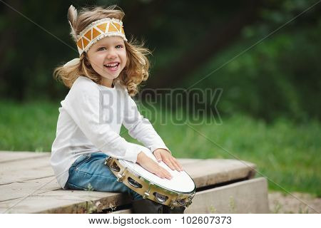little Indian girl plays the tambourine