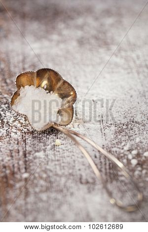 vintage sieve silver spoon with sugar powder and wooden backdrop