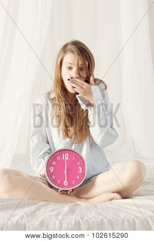 girl is sitting on bed with big pink clock. 6 a.m