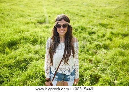 nature, summer, youth culture and people concept - smiling young hippie woman in sunglasses on green field