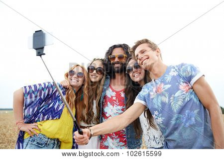 nature, summer, youth culture, technology and people concept - smiling young hippie friends in sunglasses taking picture by smartphone on selfie stick on cereal field
