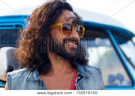 nature, summer, youth culture and people concept - smiling young hippie man in sunglasses over minivan car