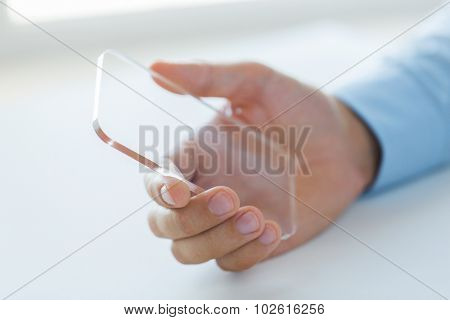 business, technology and people concept - close up of male hand holding and showing transparent smartphone at office