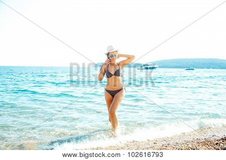 Woman In Sun Hat And Bikini Standing With Her Arm Raised To Her Head Enjoying View Of Beach