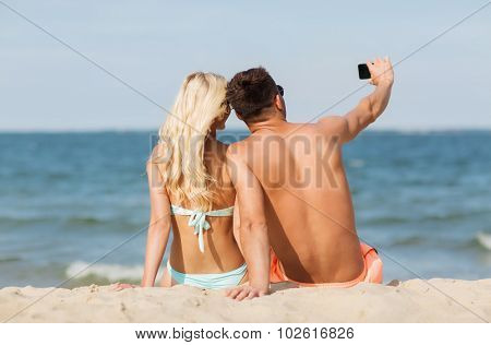 love, travel, tourism, technology and people concept - smiling couple on vacation in swimwear sitting on summer beach and taking selfie with smartphone from back