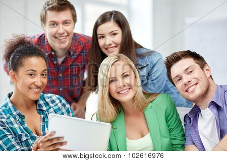 education, people, friendship, technology and learning concept - group of happy international high school students or classmates with tablet pc computer in classroom