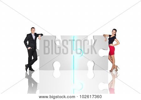 Two business people are standing near puzzle parts