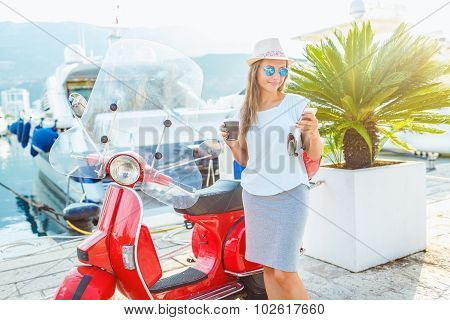 Happy Young Woman Drinking Takeaway Coffee Near Her Red Moped In The Morning