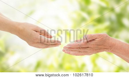 people, age, family, care and support concept - close up of senior woman and young woman reaching hands out to each other over green natural background