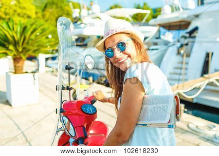 Young Cheerful Girl Driving Scooter  In The Morning