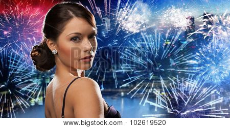 people, holidays and glamour concept - beautiful woman with diamond earring over nigh city and firework background