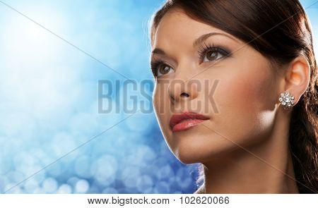 people, holidays, jewelry and luxury concept - woman face with diamond earring over blue lights background