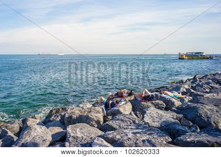 People Sleeping On Rocks At Bank Of Bosphorus