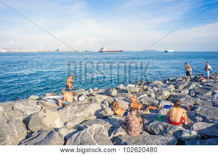 Men Relaxing On Rocks At Bank Of Bosphorus