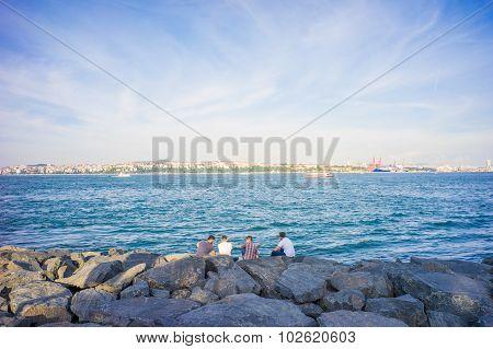 Four Men Chatting At Bank Of Bosphorus