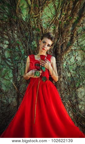 Beautiful Woman In A Red Dress With A Rose In Hand On Background Of The Old Wall Overgrown