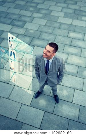 business, technology, mass media and people concept - young smiling businessman reading information from virtual screen outdoors