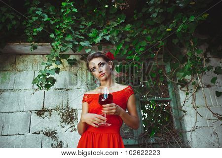 Beautiful Woman In Red Dress Standing With Glass Of Wine In The Hands Near The Old Overgrown Window
