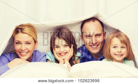 family, children and home concept - happy family with two kids under blanket at home