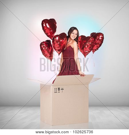 Beautiful girl inside a cardboard box with red ballooons