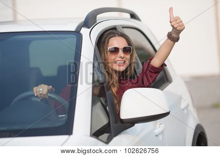 Beautiful lady showing thumb up from her car