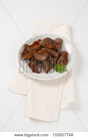 plate of cooked ear mushrooms on white place mat
