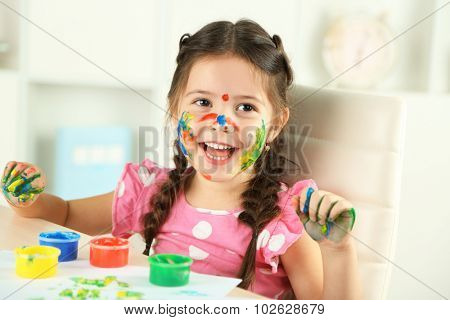 Cute little girl painting picture on home interior background