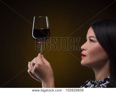 Asian sommelier woman with glass of red wine