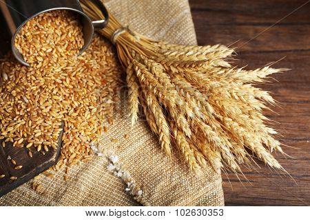 Wheat in metal cup on sackcloth, closeup