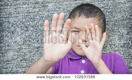 Young Asian boy using his hand to protect himself from physical abuse