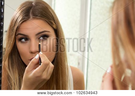Teenage girl applying eyeliner on eyes