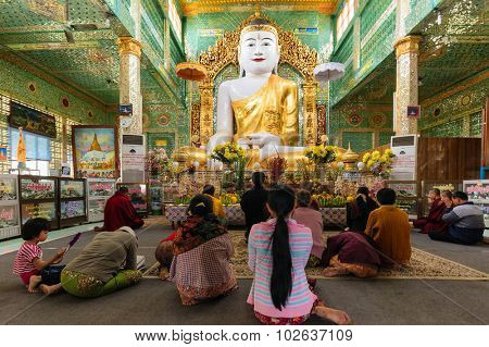 SAGAING, MYANMAR, JANUARY 16, 2015 : People are sitting on the floor for praying the large golden Buddha in the Soon U Ponya Shin Paya pagoda, Sagaing, Myanmar (Burma).