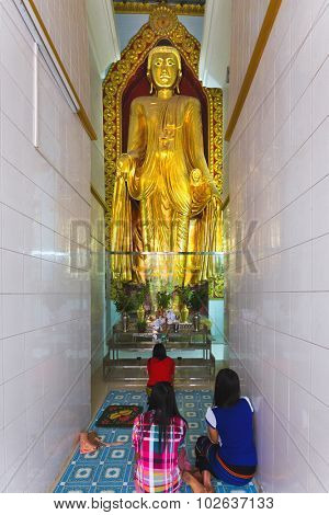 MANDALAY, MYANMAR, JANUARY 16, 2015 : People are sitting on the floor in a narrow room and praying a tall golden Buddha statue in a temple near the Mahamuni pagoda, in Mandalay, Myanmar (Burma).