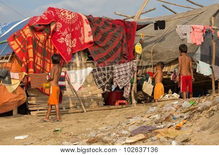 MANDALAY,MYANMAR,JANUARY 17, 2015 : Some kids are standing near a slum house in a very poor and dirty area near the river in Mandalay, Myanmar (Burma).