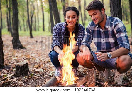 Happy beautiful couple and bonfire in the forest