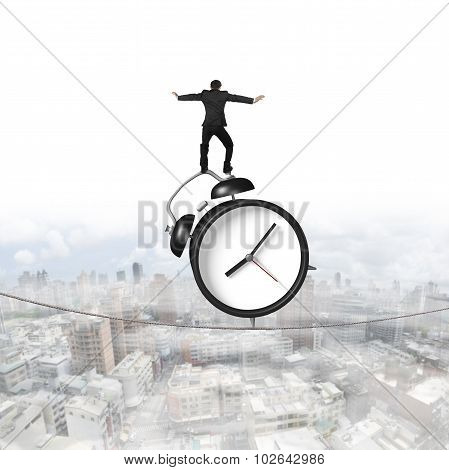 Businessman Standing On Alarm Clock Balancing Tightrope