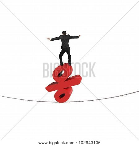 Businessman Standing On Red Percentage Sign Balancing Tightrope
