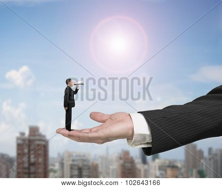 Small Businessman Using Speaker Shouting On Big Male Hand