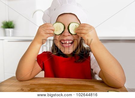 Happy Little Girl In Red Apron And Cook Hat Playing In The Kitchen With Cucumber Slices On Eyes