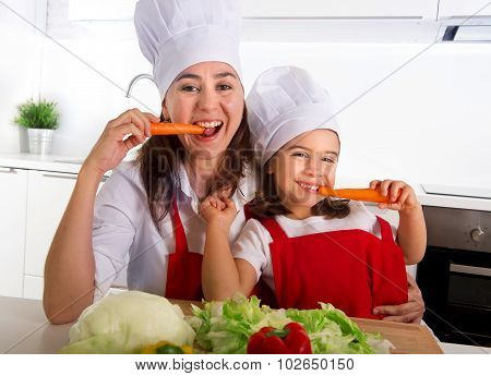 Happy Mother And Little Daughter In Apron And Cook Hat Eating Carrots Together Having Fun At Home Ki