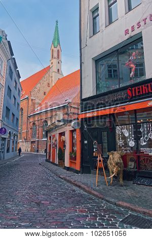 Medieval Street Of Riga's Old Town With Cafes And Restaurants Decorated For Christmas