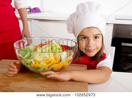 Sweet Little Girl  At Home Kitchen In Red Apron And Cook Hat Holding Vegetable Salad Bowl