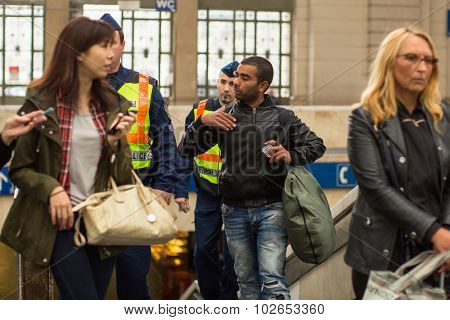 BUDAPEST, HUNGARY - SEP 20, 2015: Hungarian police detain one of Syrian refugees at Budapest Keleti railway station. Hungarian authorities have closed the border with Serbia for refugees on 15 Sept.