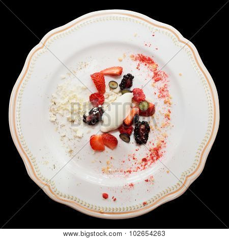 Berries with ice cream on plate, isolated on black background