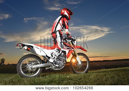 Motocross rider standing on motocycle during sunset