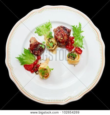 Duck meat with berries and ravioli in plate, isolated on black